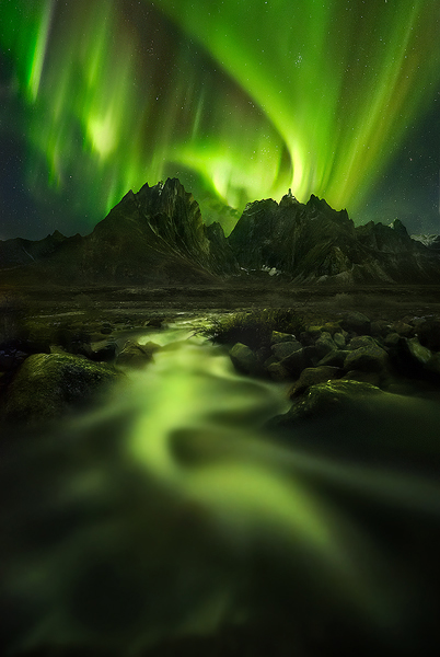 An amazing aurora show reflected in the waters of a small stream and over the high peaks of Yukon's north.