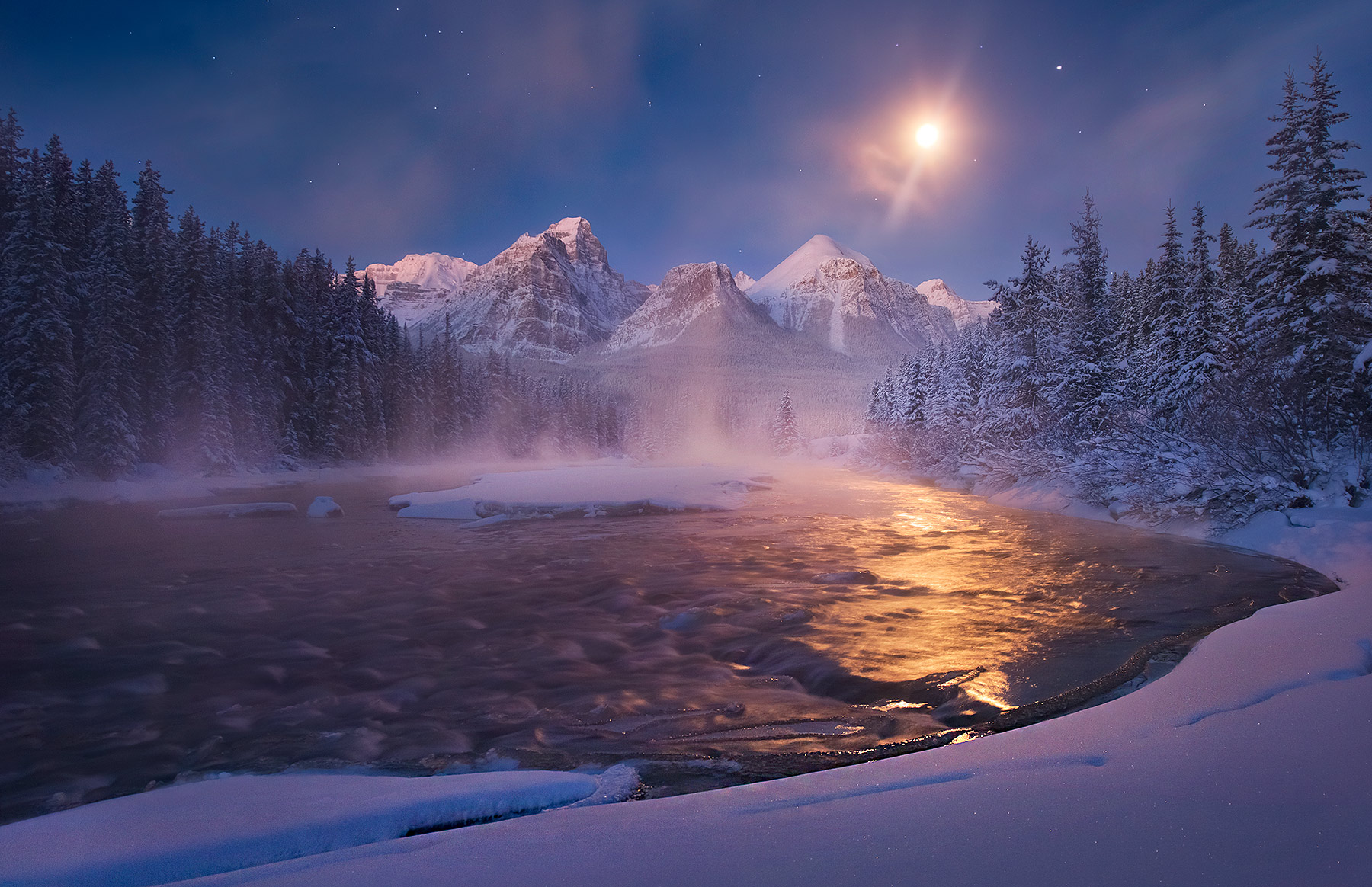 The moonlight sets over high peaks in the Canadian Rockies. Cold temperatures well below zero cause the formation of beautiful...
