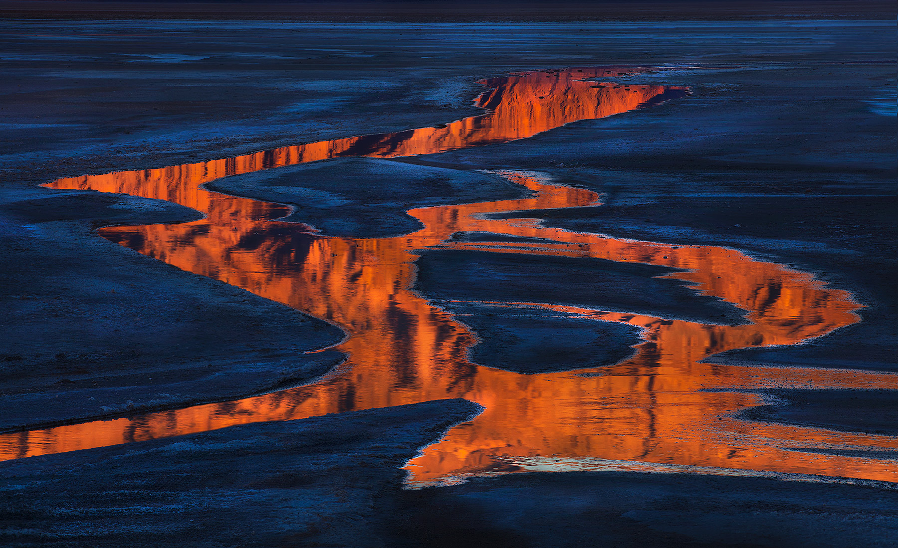 Reflected sunrise light in a winding stream located on the floor of Death Valley, California.