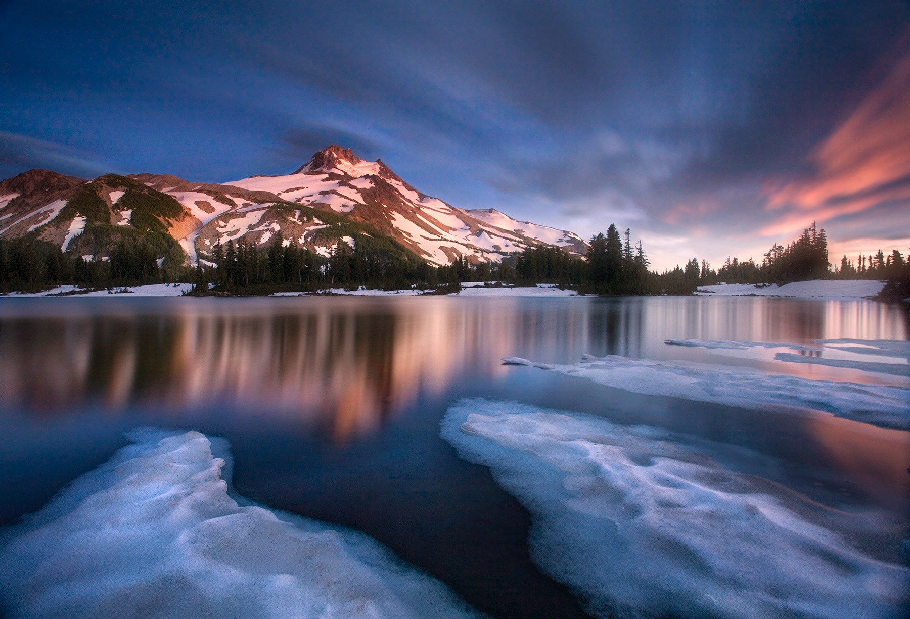 Long exposure streaks the clouds passing over Oregon's Mount Jefferson reflected in an icy lake.
