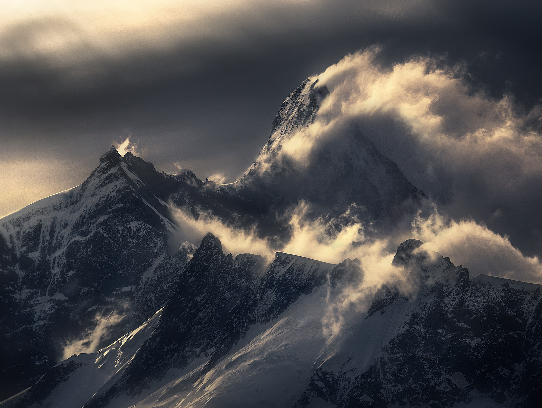 The great Mount Aspiring rips through the clouds amidst high winds one cold summer day.