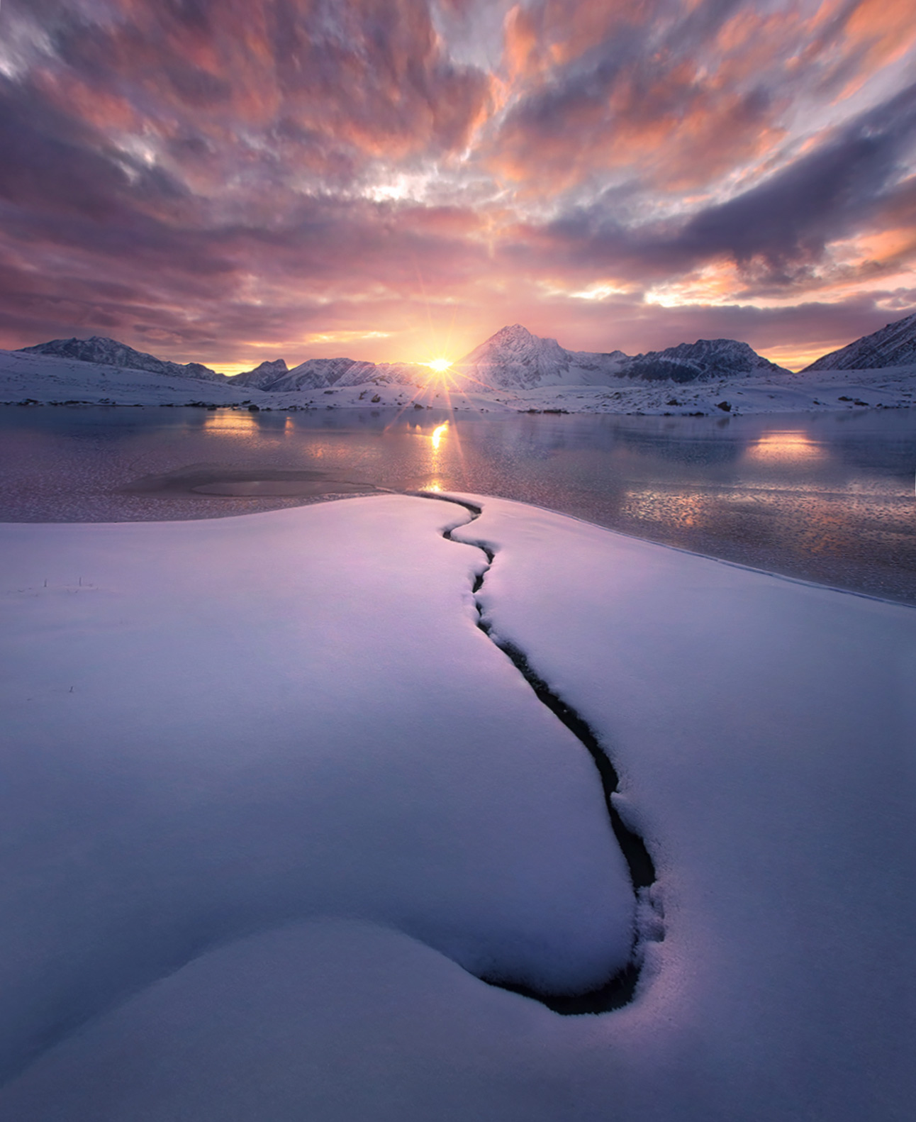 The solitary unfrozen line of a burried stream disappears into a frozen lake and the sunset beyond, photographed from a very...