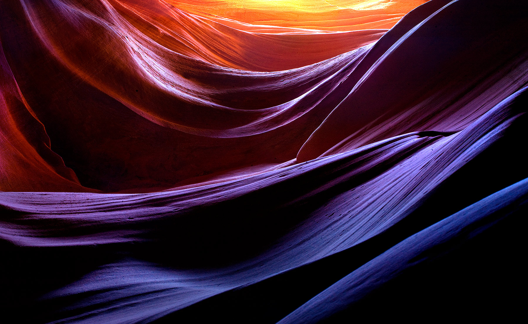 Looking up from the depths of a hundred-foot deep slot canyon at layers of sandstone. The various rich colors and hues present...