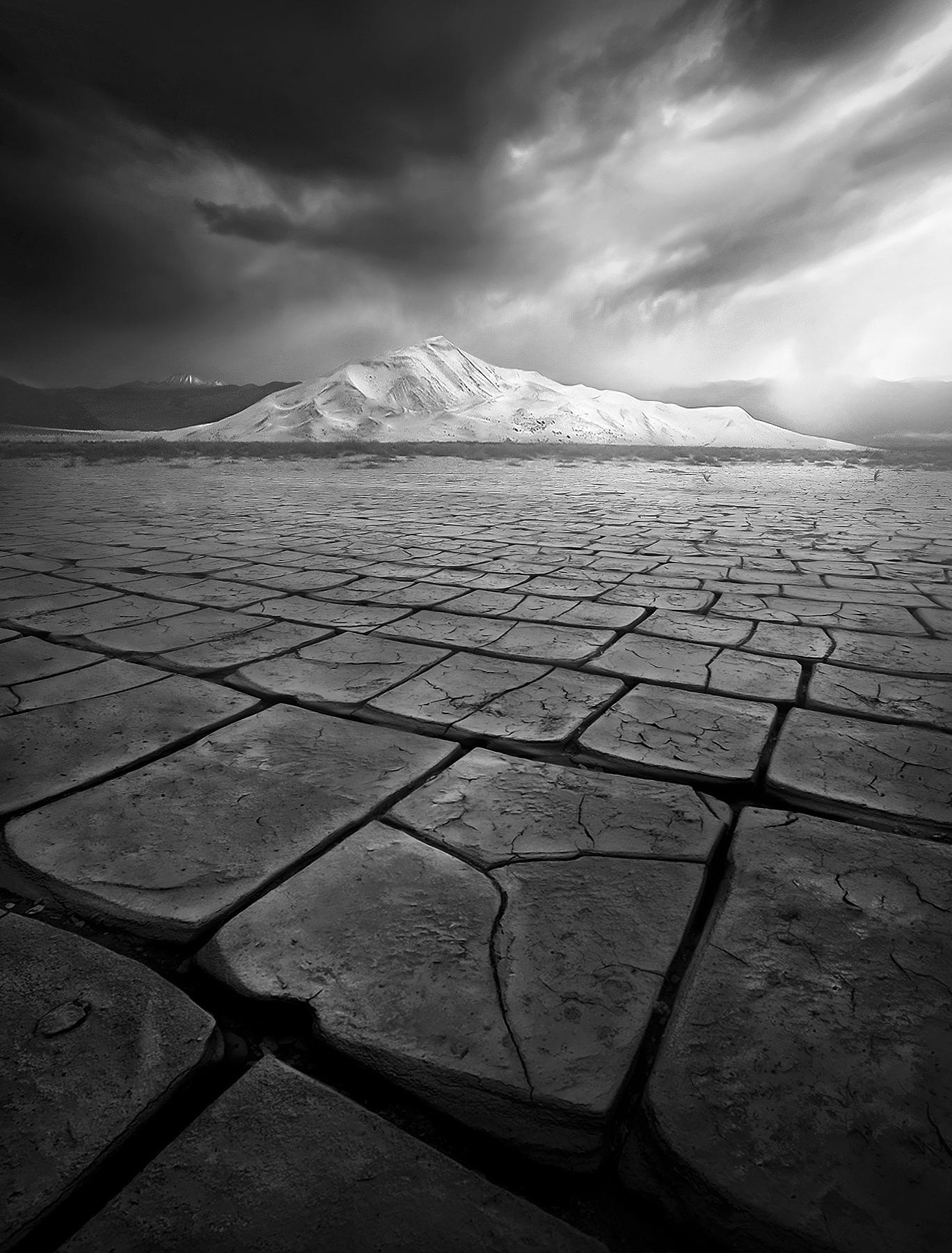 Amazingly uniform cracks on this dried playa next to Death Valley's Eureka Dunes under dramatic skies.