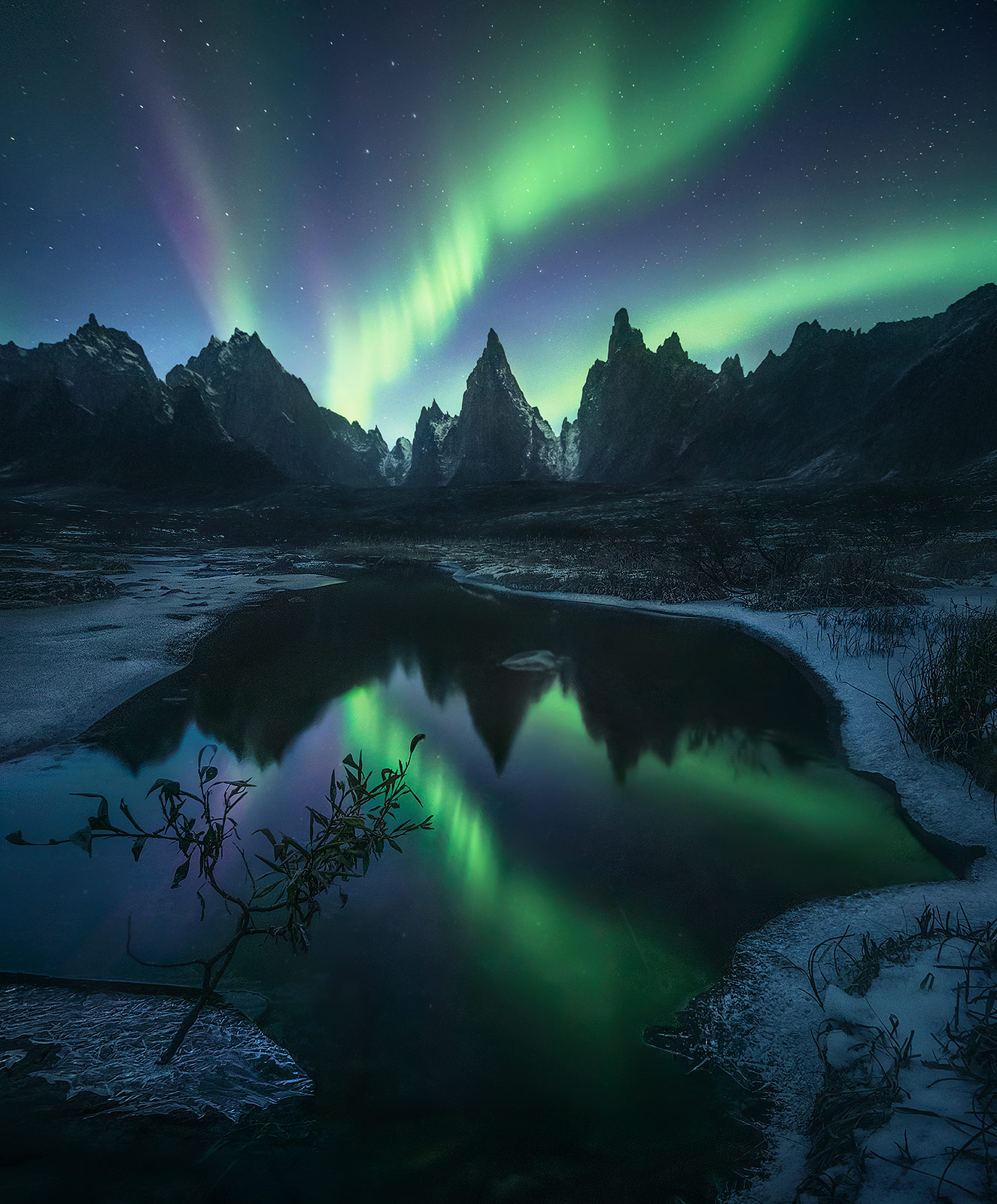 Twilight fades away as the aurora appears over rarely photographed peaks deep in the wilderness of the Yukon.