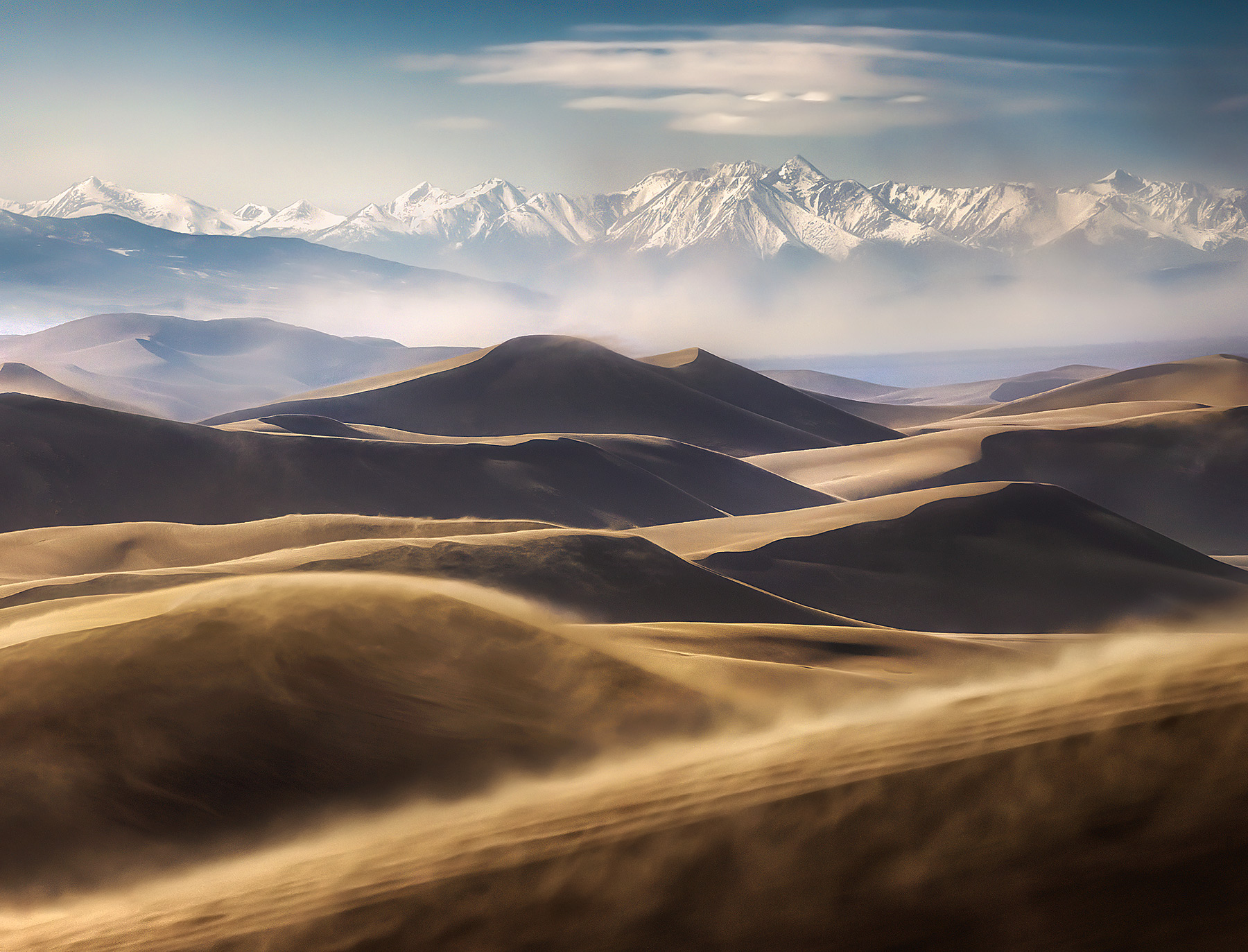 Telephoto layers of dunes and distant mountains amidst blowing sands in Colorado