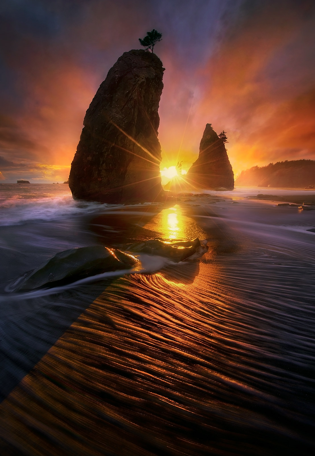 An explosion of dramatic lighting seen from the Olympic Coast at sunset. Foamy seawater rushes by through the long exposure in...