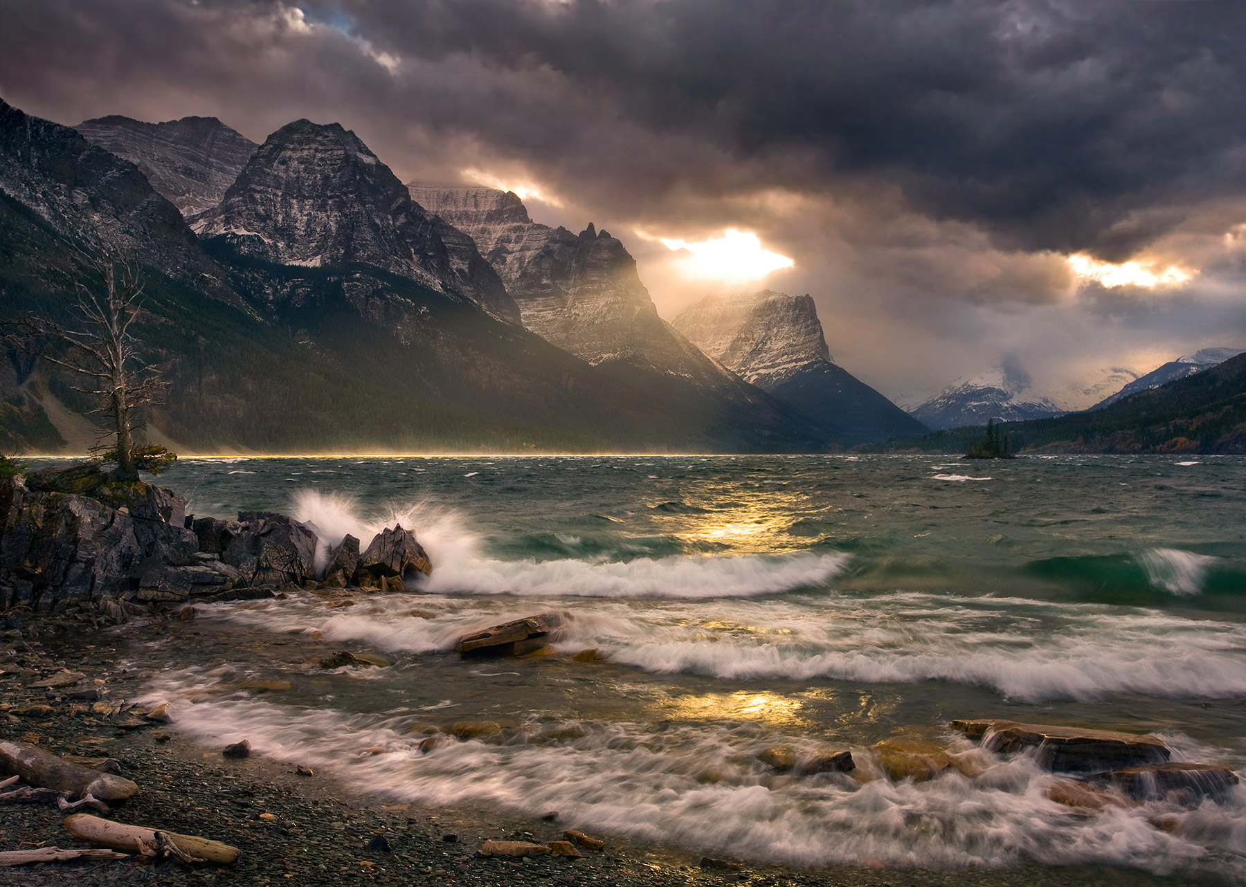 Stunning dramatic light beams through stormy skies illuminating the waters of Saint Mary lake and the waves crashing against...