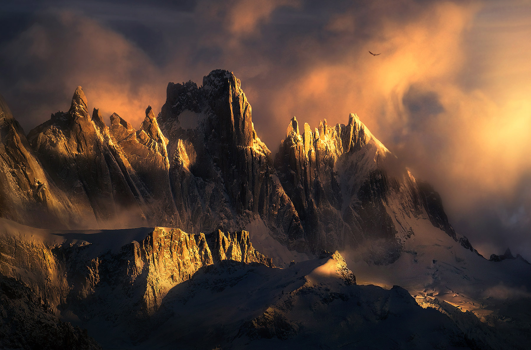 Enormous, sharp peaks high in the Patagonian Andes mingle with the soft clouds one beautiful morning.