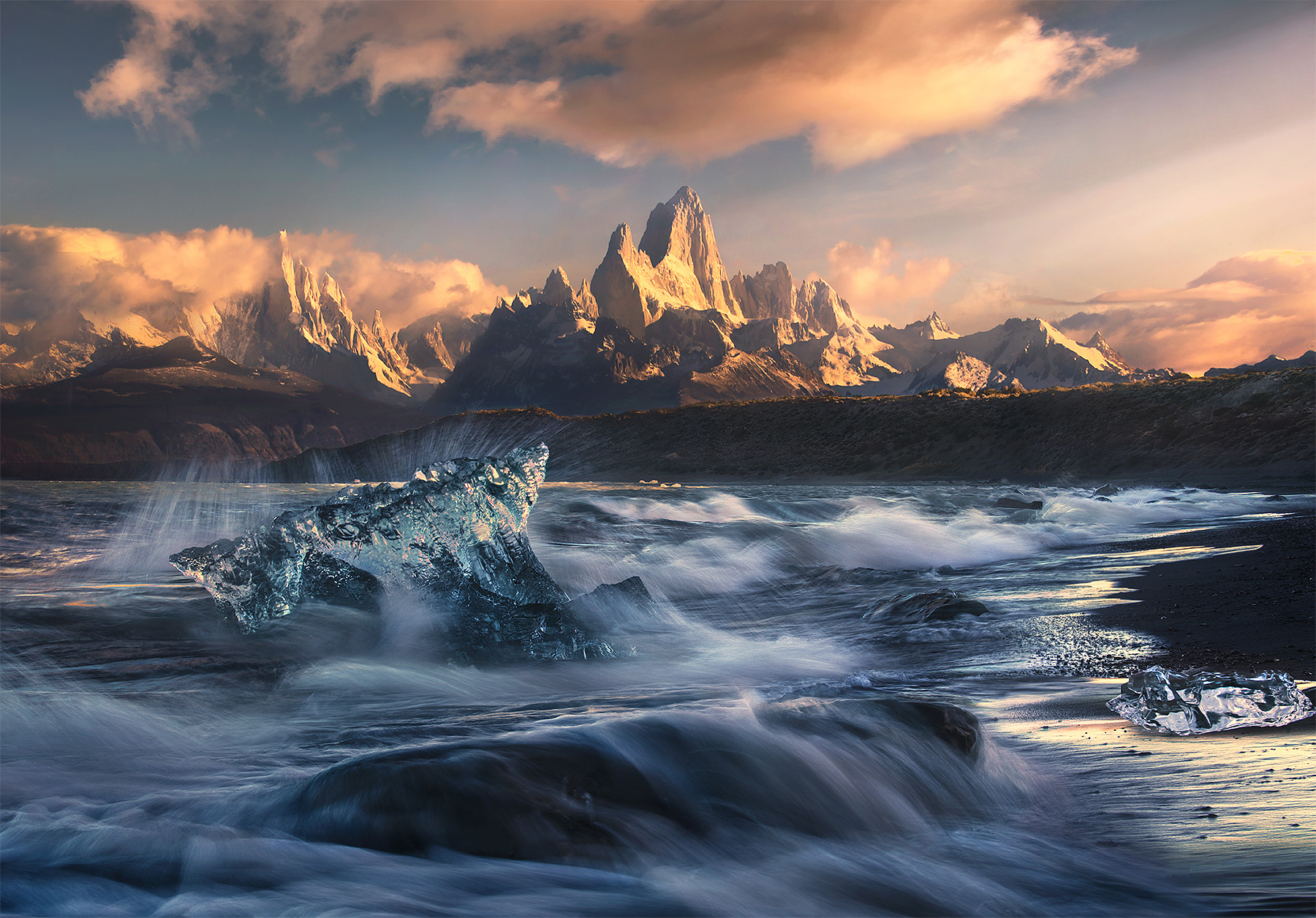 A unique view of Fitz Roy and Cerro Torre from a distant lakeshore catching some big wave action and a few icebergs one beautiful...