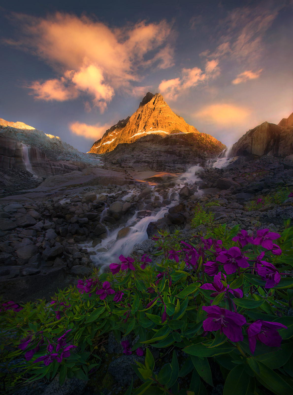 Lush summer wildflowers adorn the glacial hillside. Above, mountains reach into the sunset sky surrounded by high waterfalls...