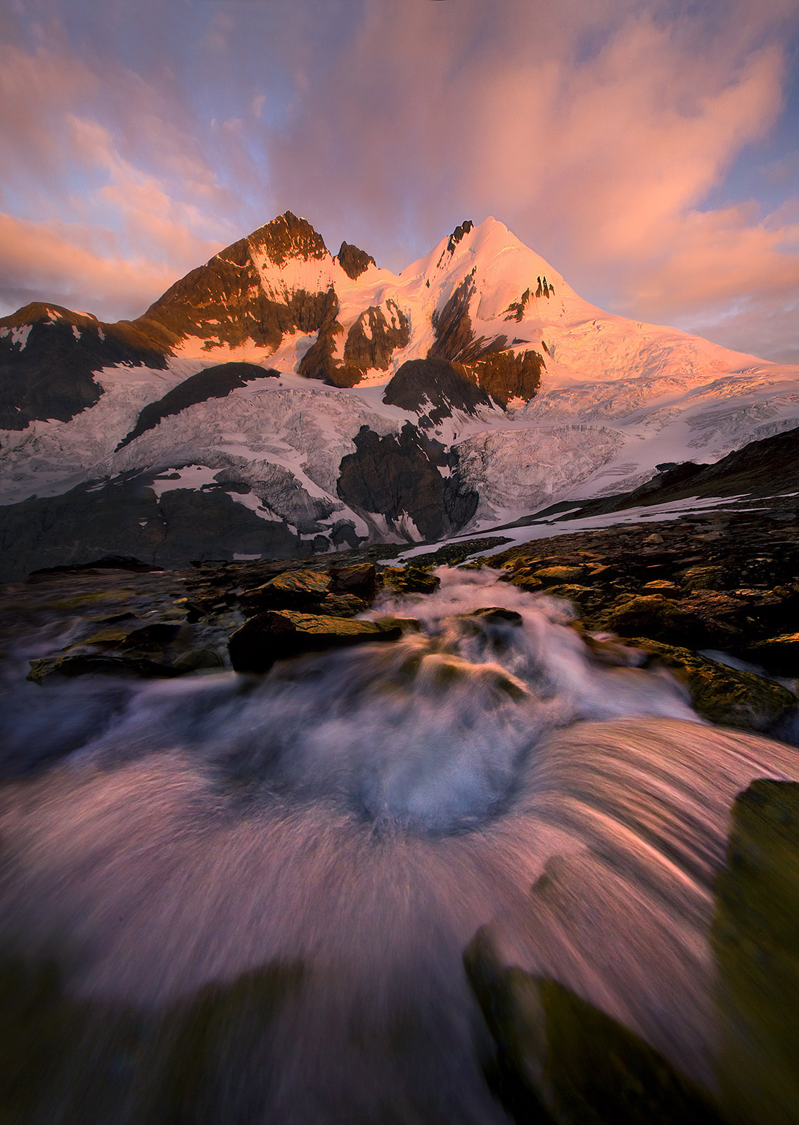 Cascades catching the light of sunrise looking down a steep talus field towards a glacial valley and high peaks in the distance...