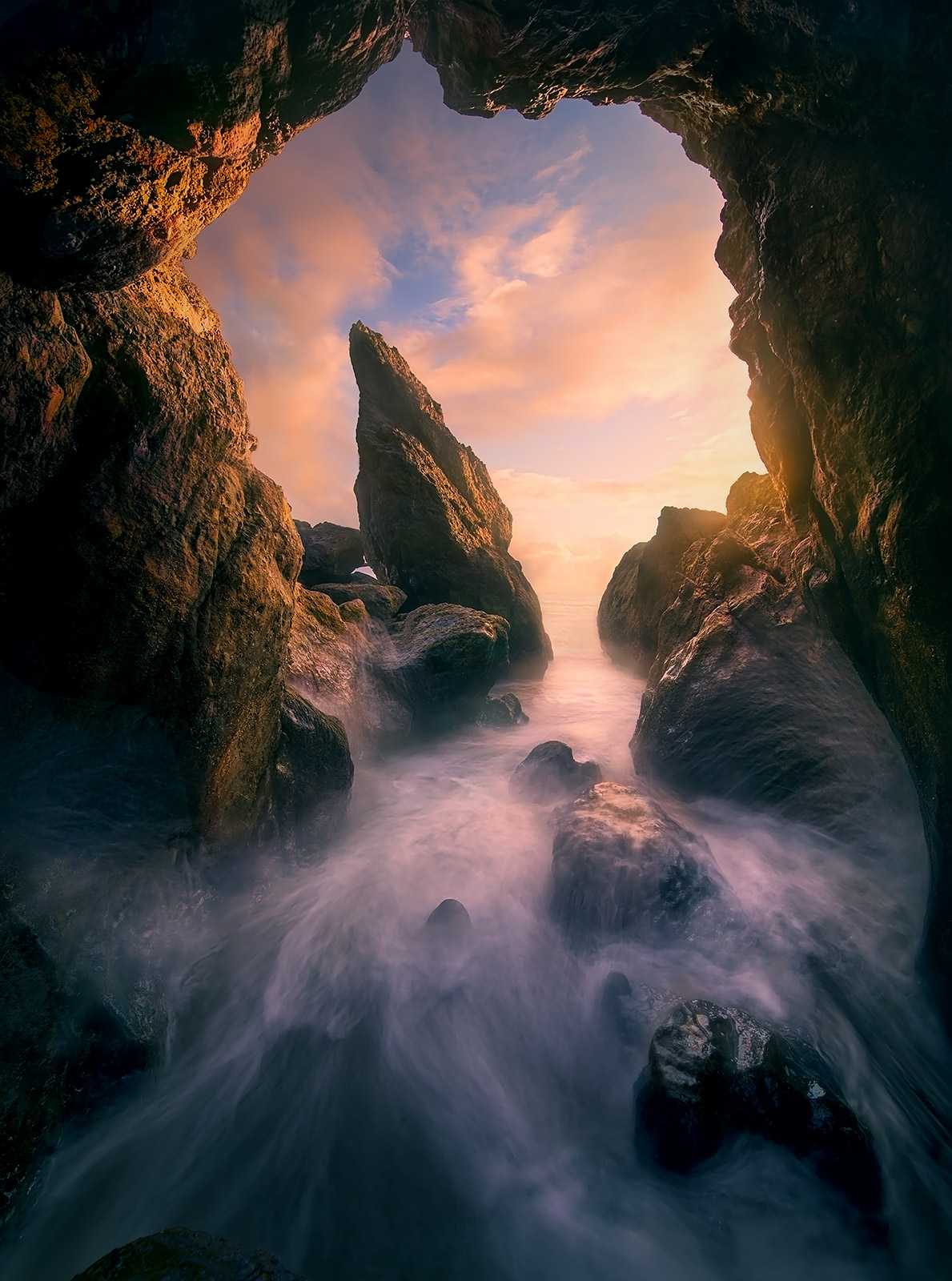 Sunset light and waves inside an ocean cave in Washington.