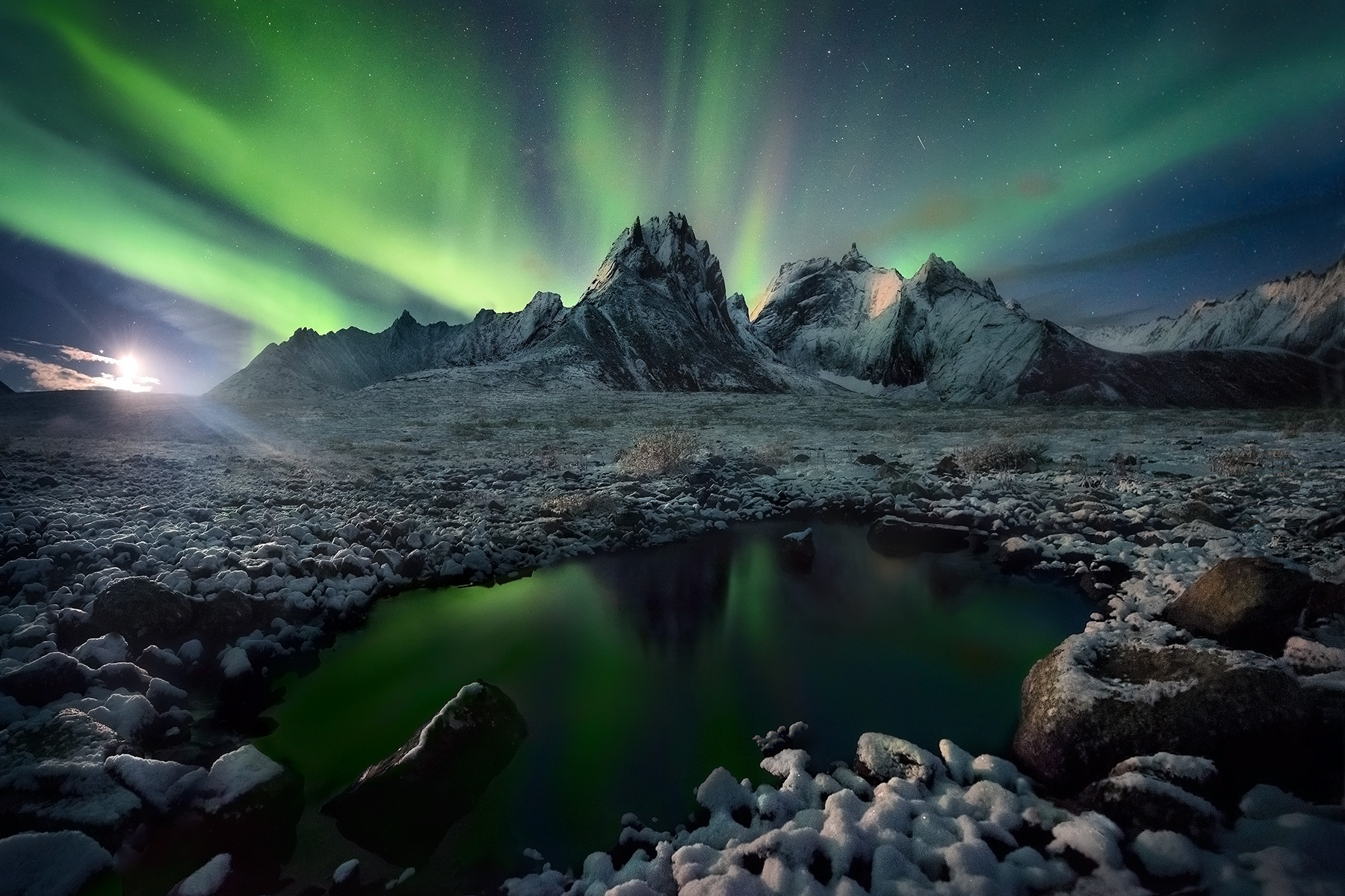 The Aurora and light from a faint moon appearing over mountains in the Tombstone range, Yukon and a fresh early-season snowfall...