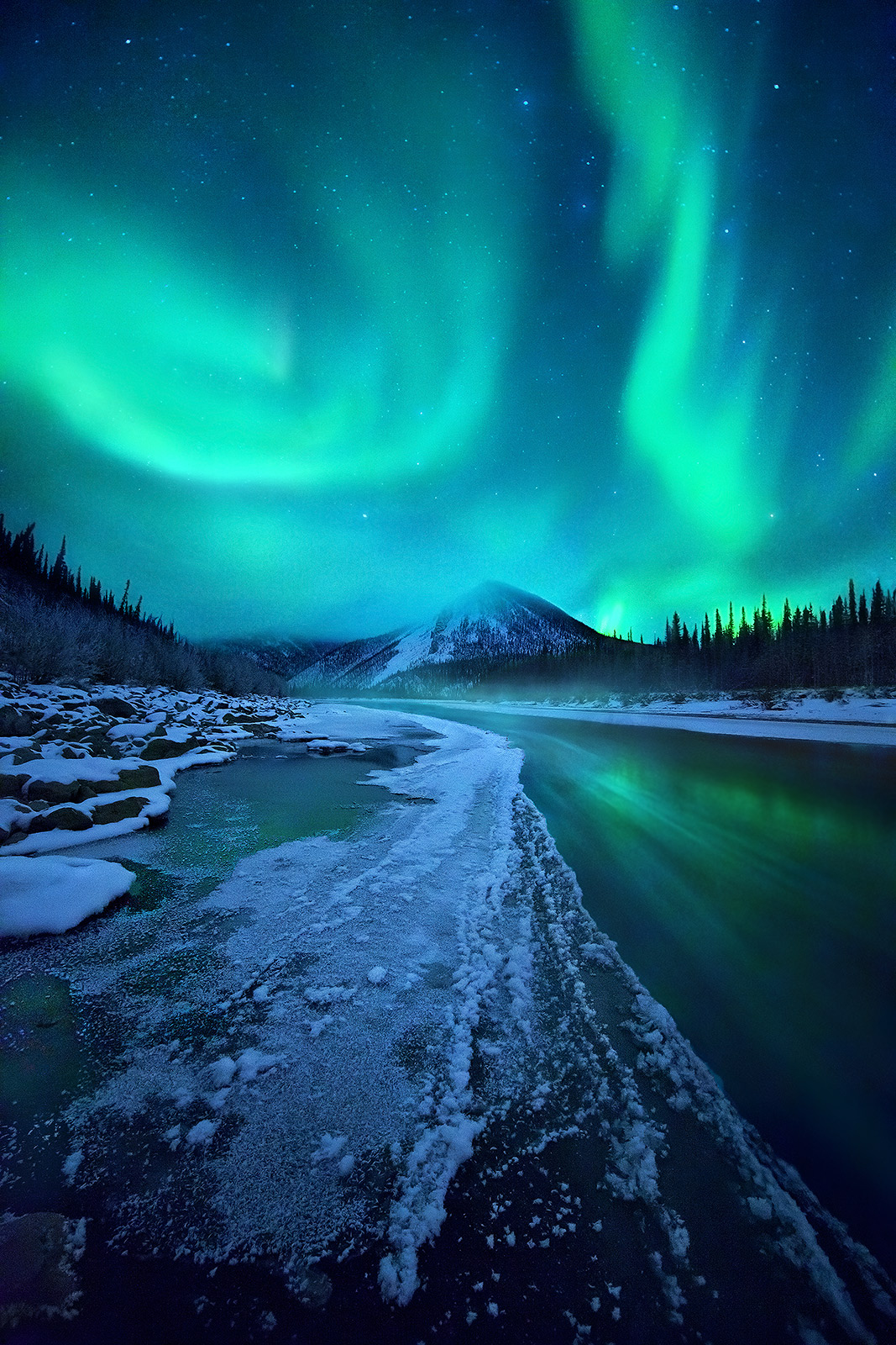 Spectacular colors of the Aurora over the Ogilvie Mountains, Yukon Territory. Streaks in the water from ice floating down river...