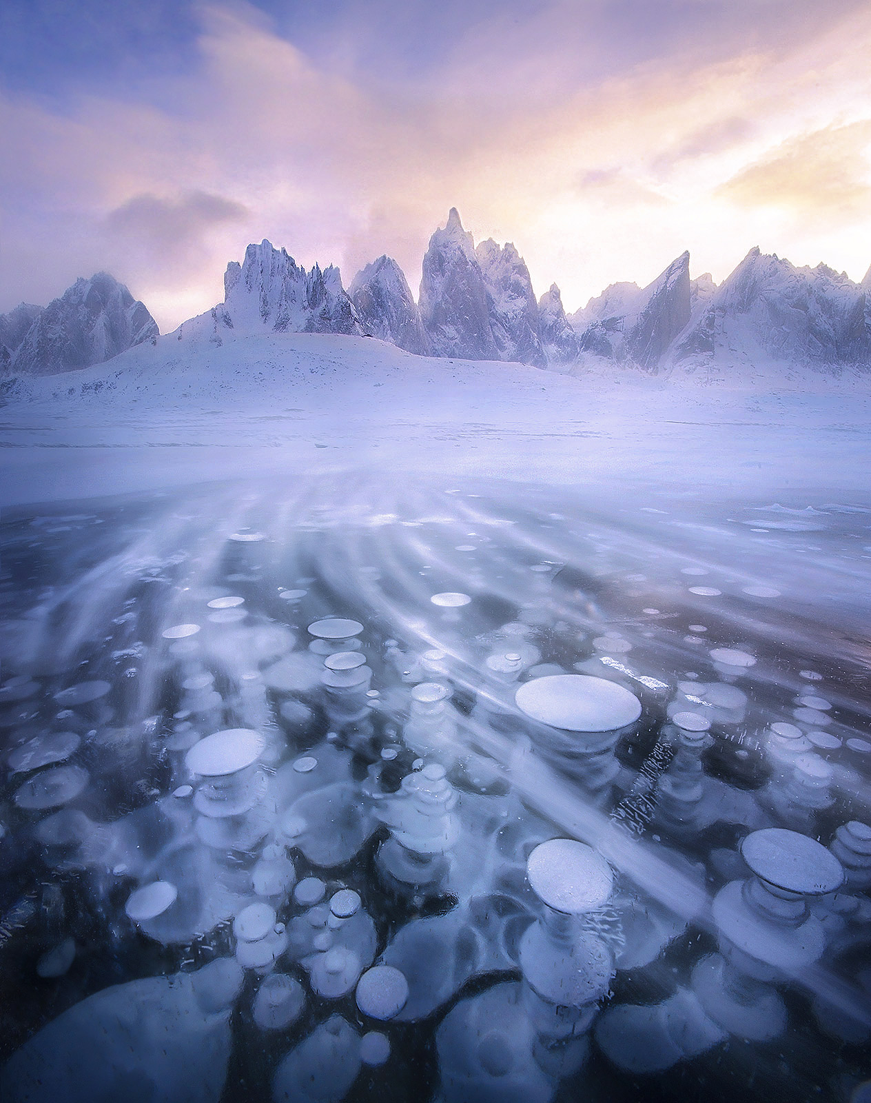 This photograph of ice bubbles and blowing snow on a lake underneath Mount Monolith and other peaks in the Yukon probably has...