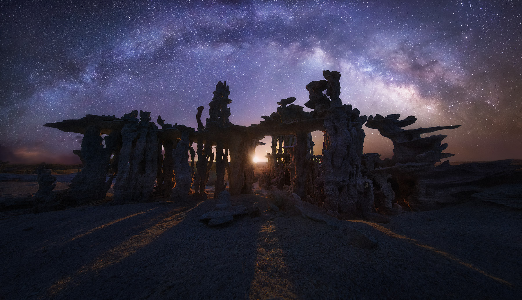 The light of the crescent MOON rises between towers of sand tufa rock. Three images were used side by side to record the...