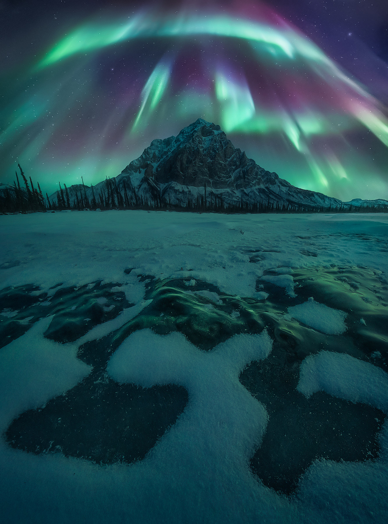 The aurora lights up high peaks above the Arctic Circle in Alaska in midwinter