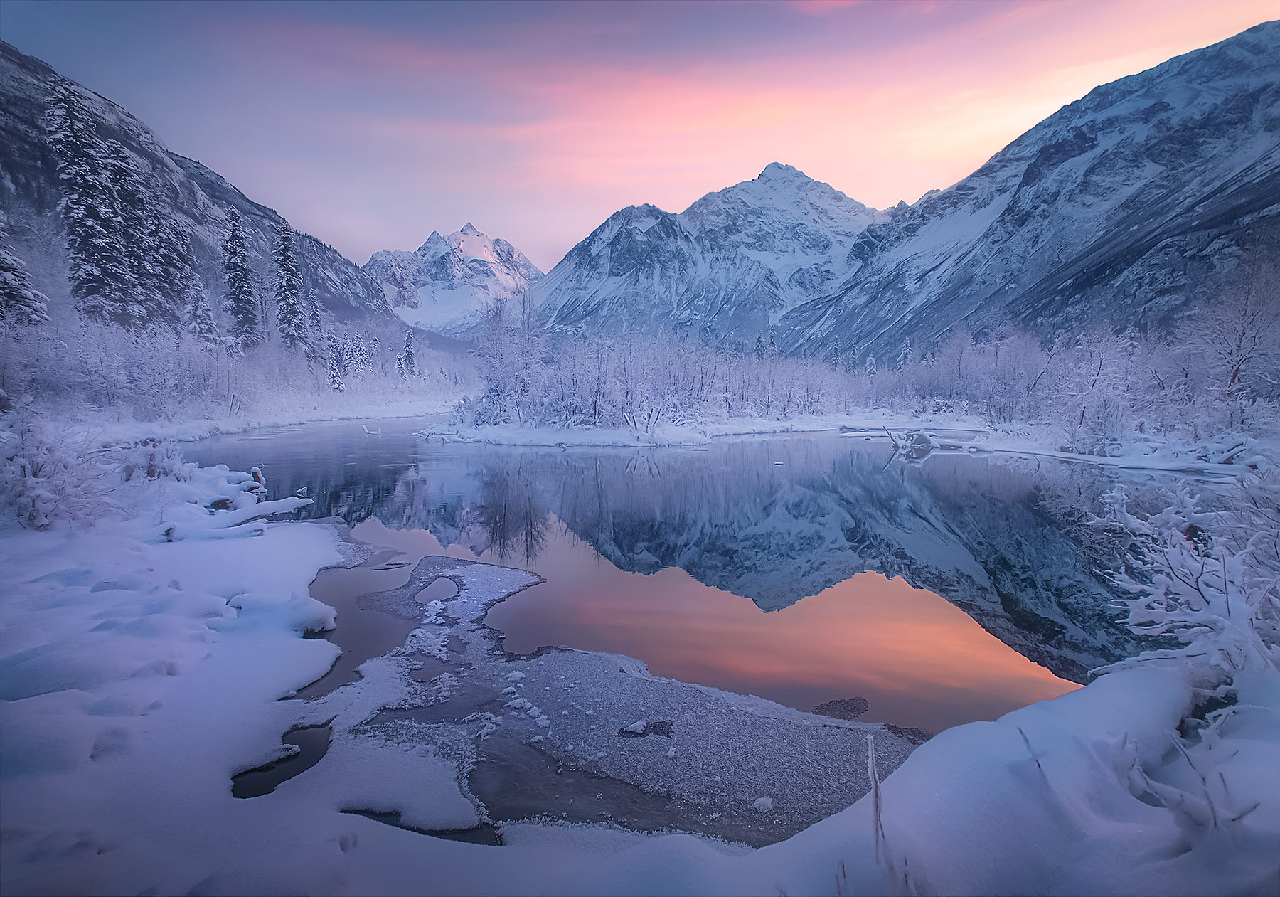 Peaks in Alaska catch the soft winter's light reflected in warm groundwater pools.