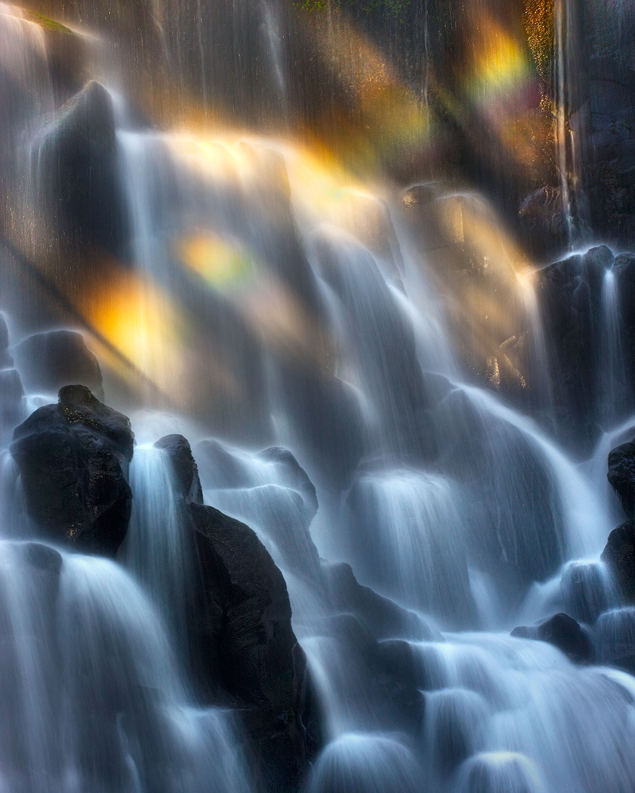 The last light of sunset creating rainbows across this beautifully terraced waterfall in the Mount Hood wilderness, Oregon.