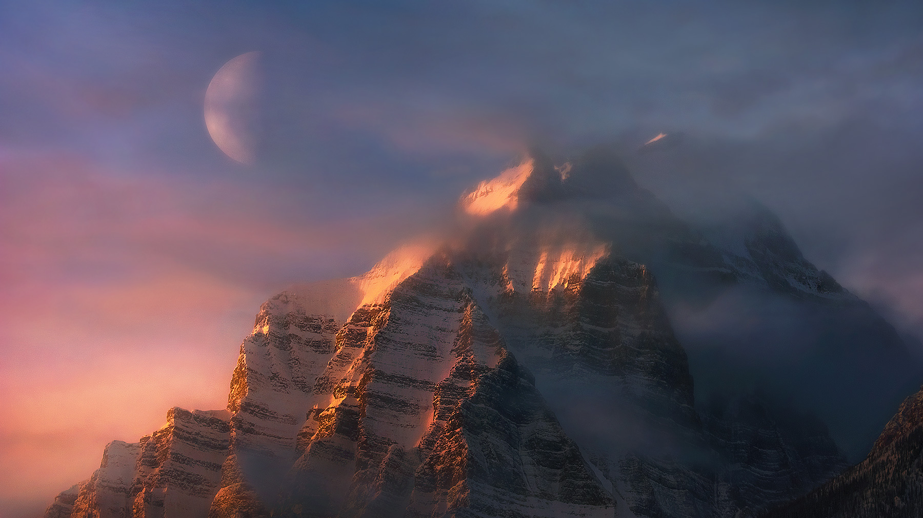 The summit of Mount Temple from a distant viewpoint as the sun rises and the moon sets at 300mm.