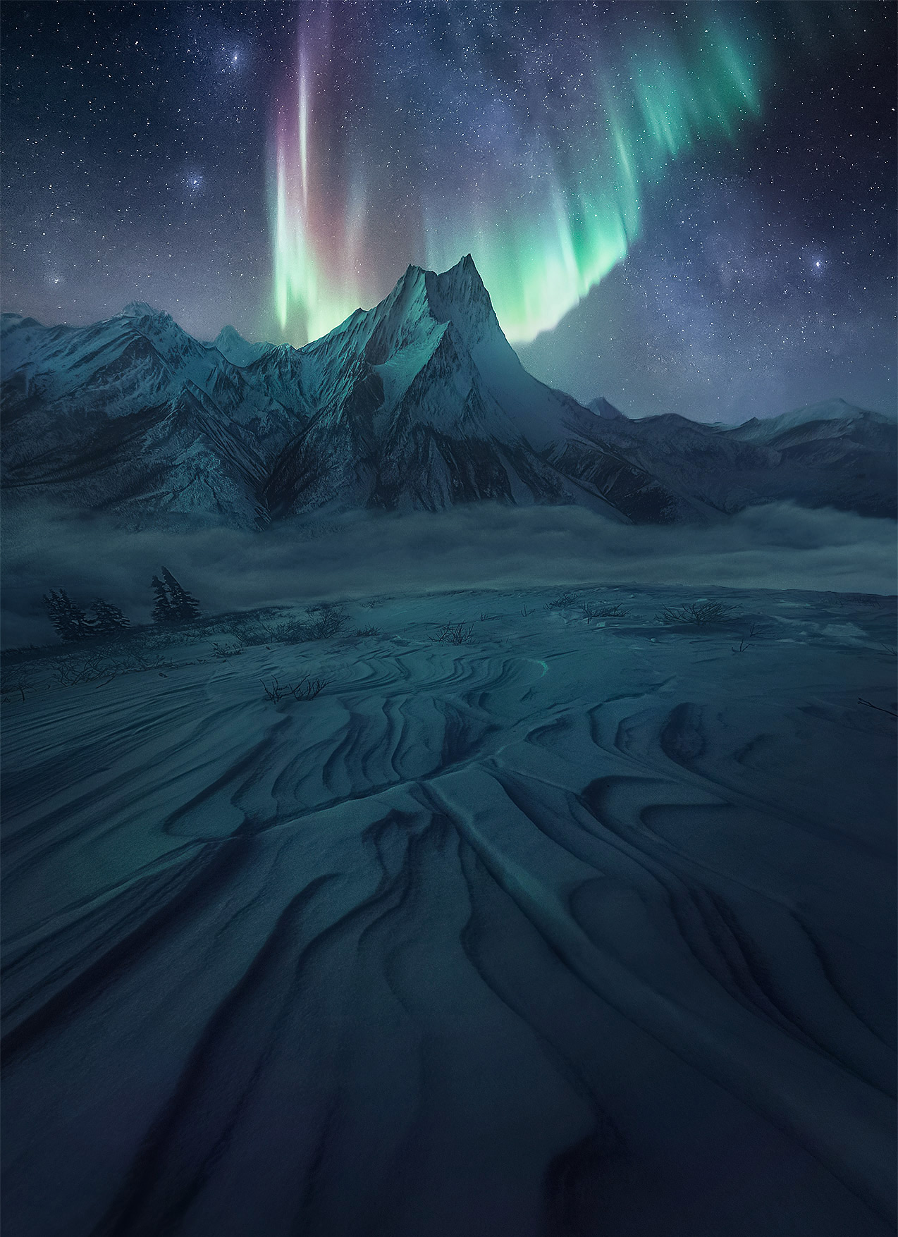 High peaks of Arctic Alaska depicted in faint moonlight below the aurora and Northern band of the Milky Way
