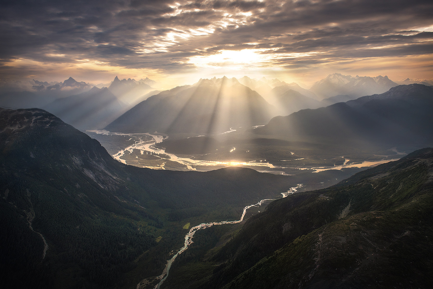 Light pours through the clouds over the Stikine River, BC, one hazy summer morning in the Boundary Ranges.