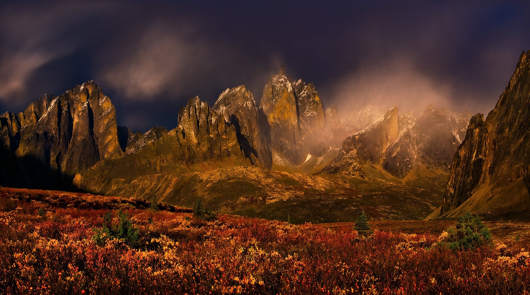 Dramatic light over the great peaks of the Ogilvie Mountains amidst rich Autumn colors. Yukon territory, Canada. The photograph...