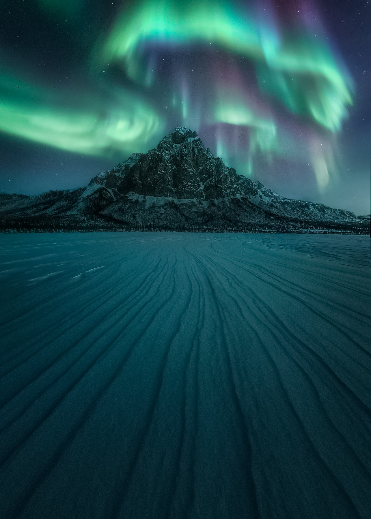 Sastrugi lines in the compacted snow make for some fascinating views atop a frozen lake in Arctic Alaska, complimenting the aurora...