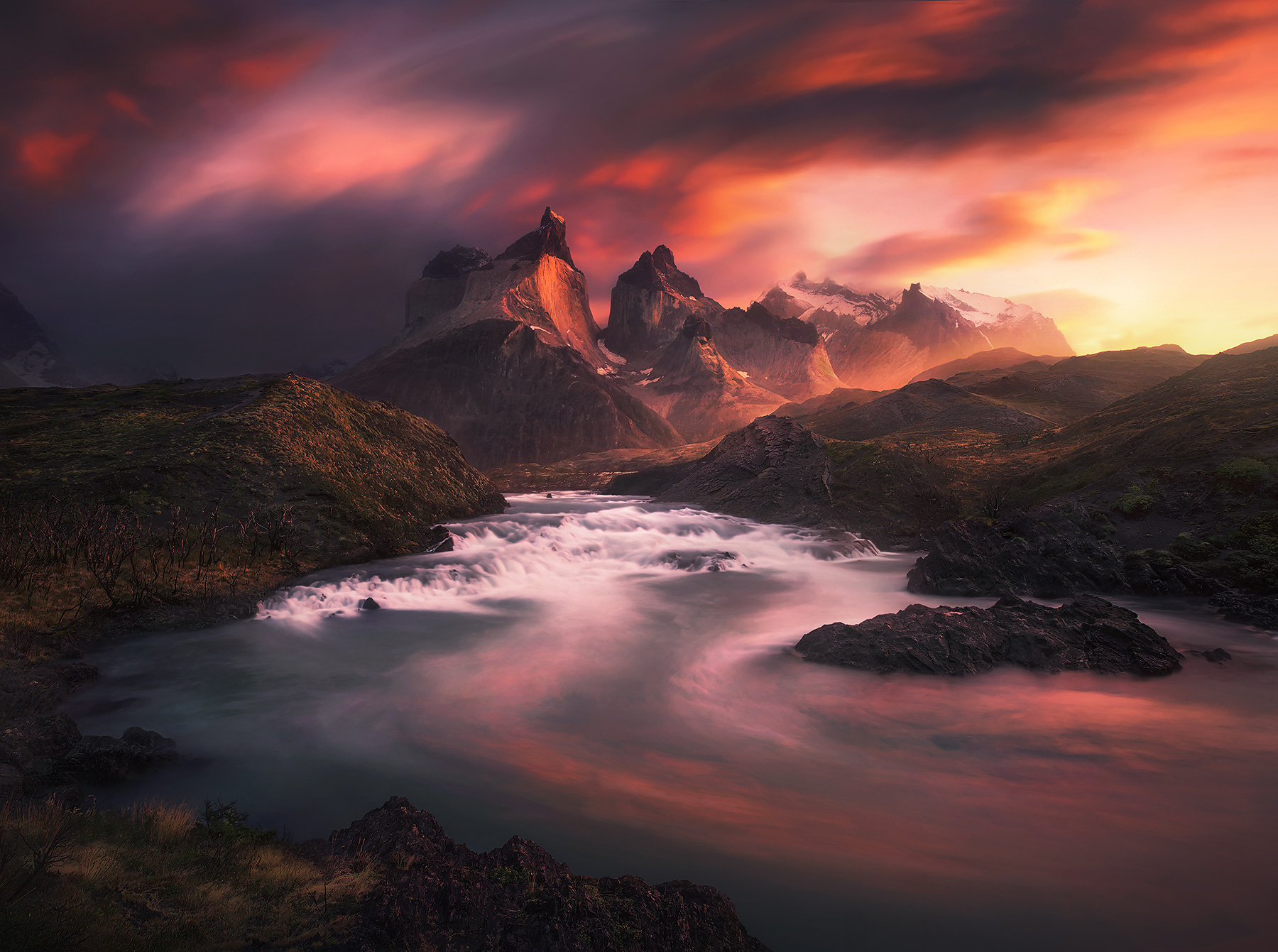 A unique view of the famous Salto Grande Falls and Torres Del Paine, bathed in sunrise colors.