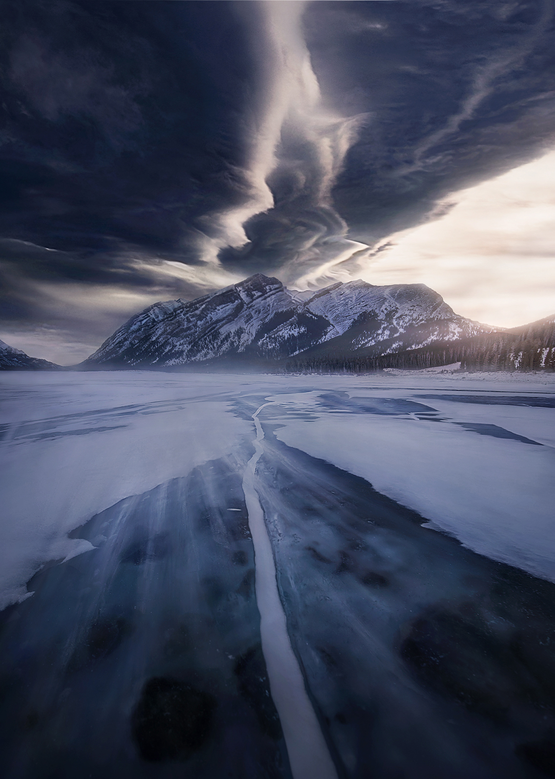 Blowing snow over ice and wild shapes in the sky formed by a lenticular wave cloud align for a cold and dramatic scene.