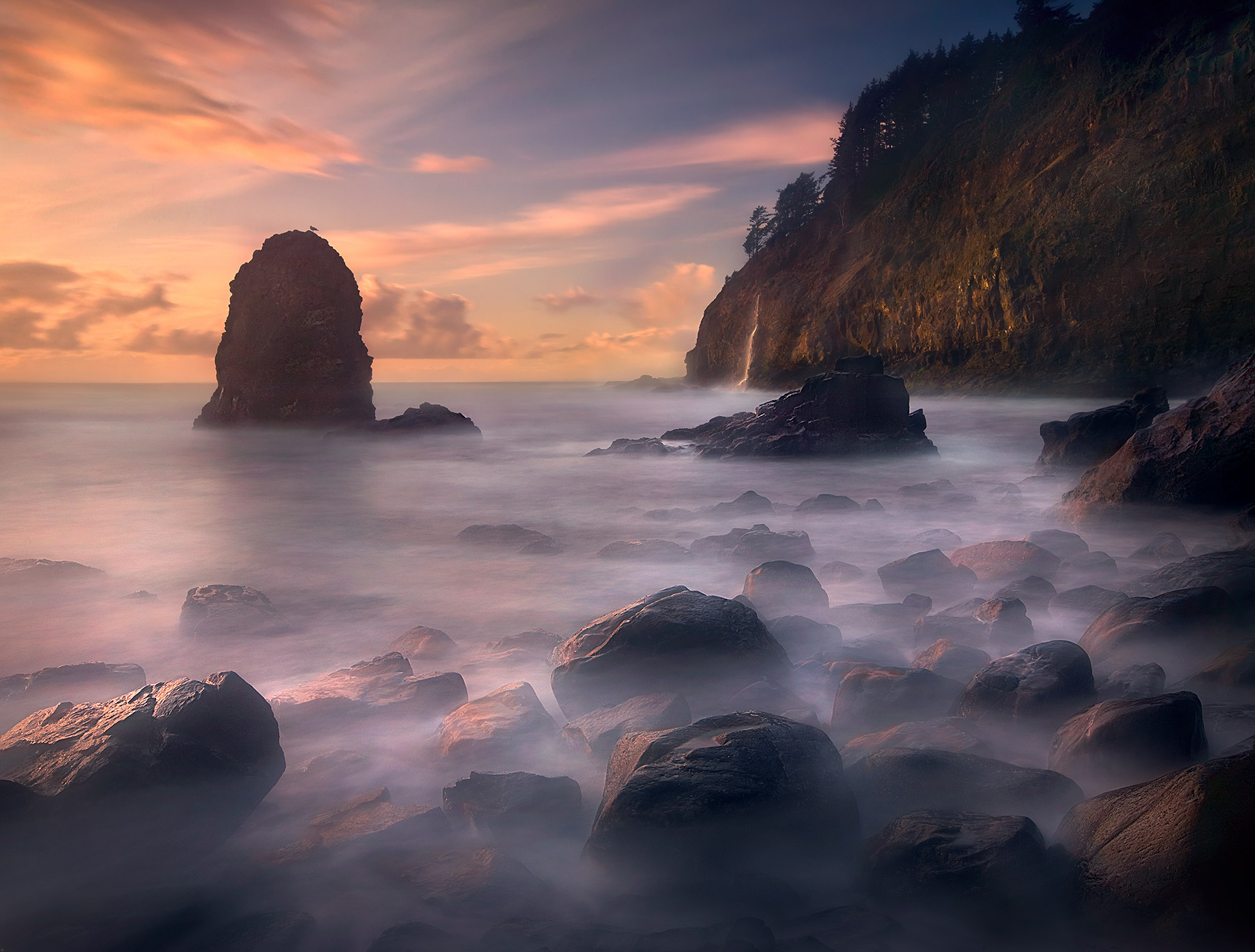 Long exposure turns Pacific waters to mist at sunset on Oregon's Coast. A waterfall pours off the cape in the background.