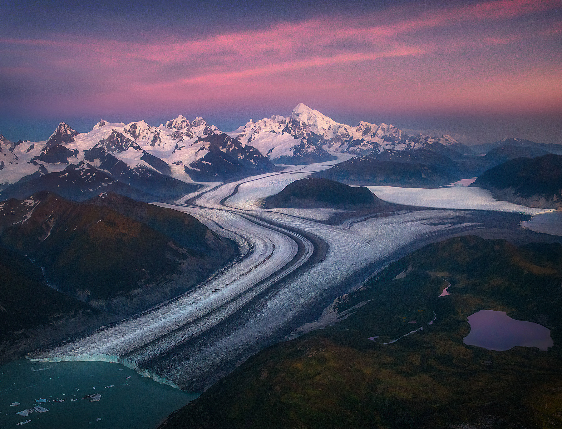 Enormous mountains and glaciers more than 20 miles long envelope an Alaskan landscape adorned with fall colors at twilight.