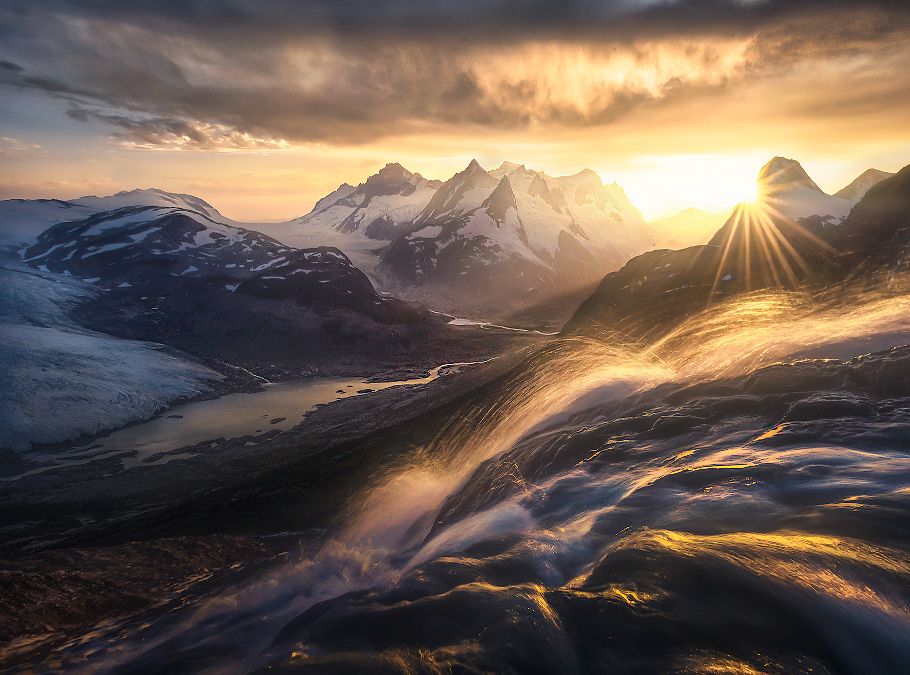 A beautiful sunset reflects off cascading waters descending into the glacial valley and rivers below.  Taken just feet from one...